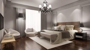 Elegantes Hotelzimmer mit Doppelbett und Sessel als Schlafzimmer